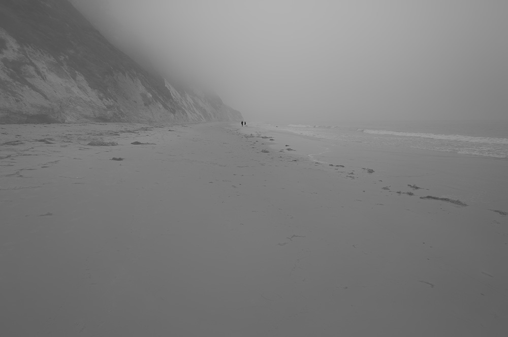 two smaller figures walking on beach BW s.jpg